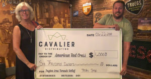 Cindy (Trolley Stop) and Aaron (Cavalier Distributing) showcasing the big check after a successful fundraising event